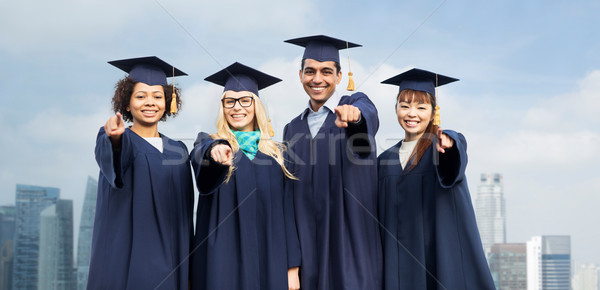 Stock photo: students or bachelors pointing at you over city