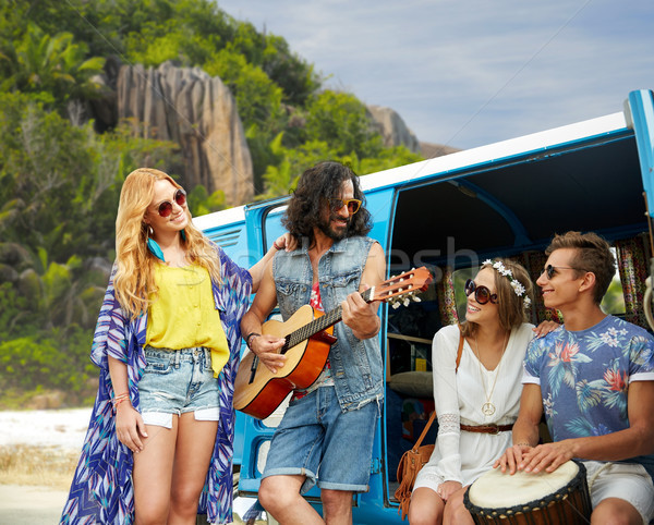 hippie friends playing music at minivan on beach Stock photo © dolgachov