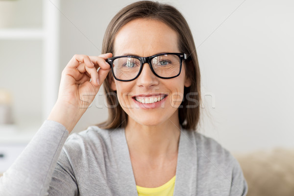 happy smiling middle aged woman in glasses at home Stock photo © dolgachov