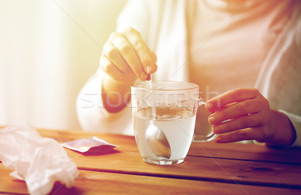 woman stirring medication in cup with spoon Stock photo © dolgachov