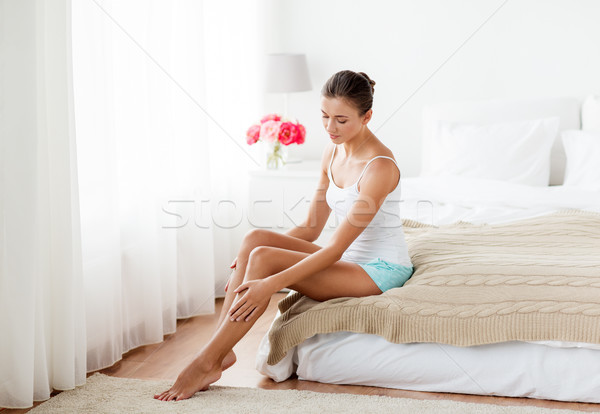 beautiful woman with bare legs on bed at home Stock photo © dolgachov