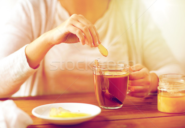 close up of ill woman drinking tea with ginger Stock photo © dolgachov