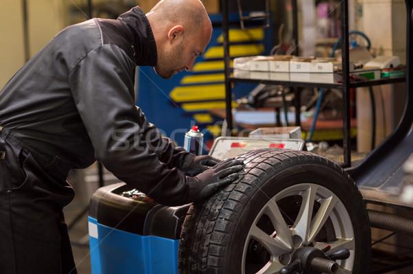 auto mechanic balancing car wheel at workshop Stock photo © dolgachov