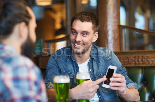 friends with smartphone drinking green beer at pub Stock photo © dolgachov