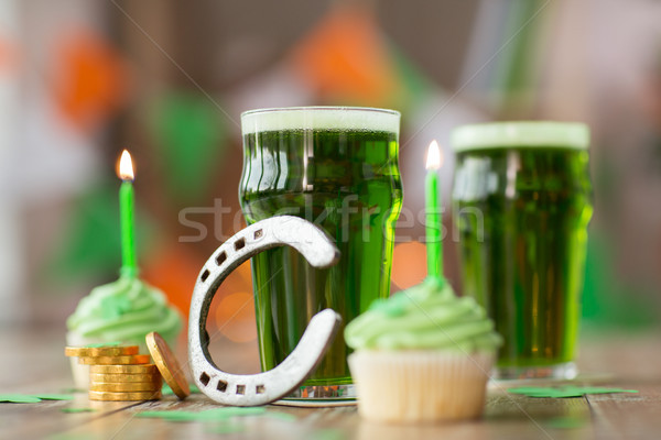 glass of beer, cupcakes, horseshoe and gold coins Stock photo © dolgachov