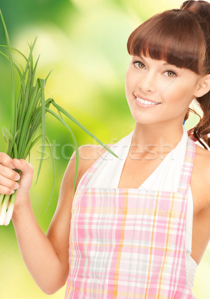 beautiful housewife with spring onions over green Stock photo © dolgachov