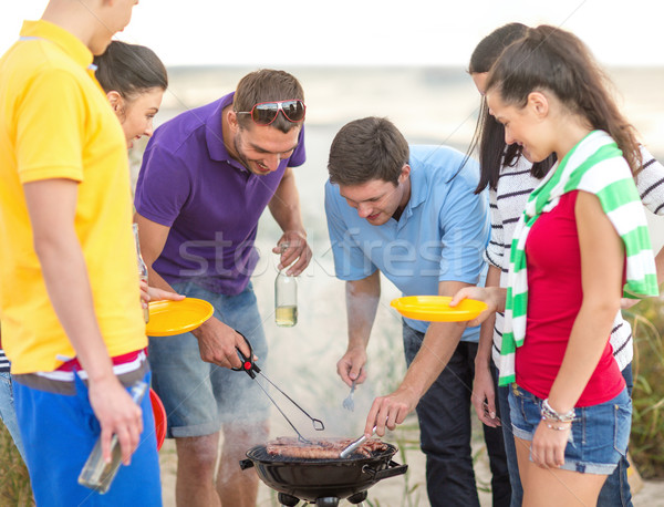 group of friends having picnic on the beach Stock photo © dolgachov