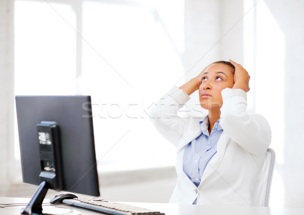 stressed african woman with computer Stock photo © dolgachov