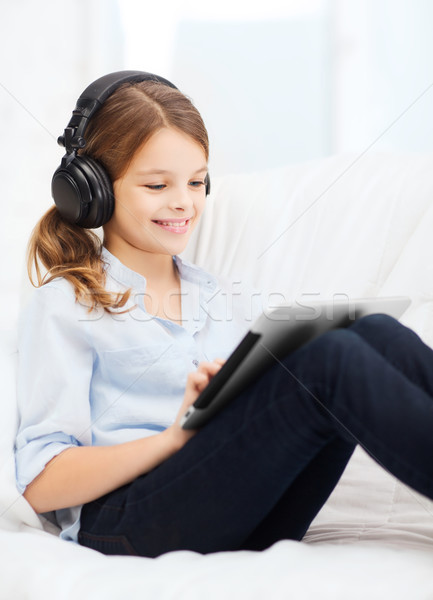 girl with tablet pc and headphones at home Stock photo © dolgachov