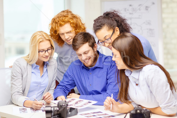smiling team with photocamera and images in office Stock photo © dolgachov