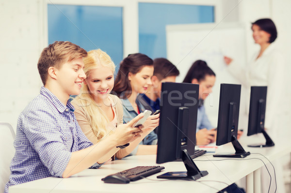 students with computer monitor and smartphones Stock photo © dolgachov
