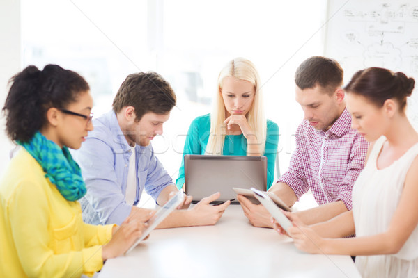 serious team with table pc and laptop in office Stock photo © dolgachov