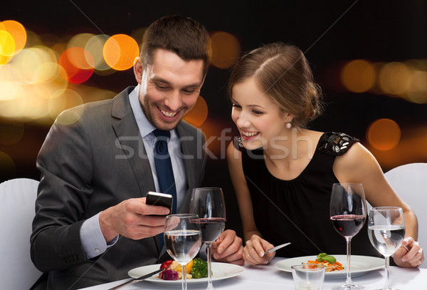 smiling couple eating main course at restaurant Stock photo © dolgachov