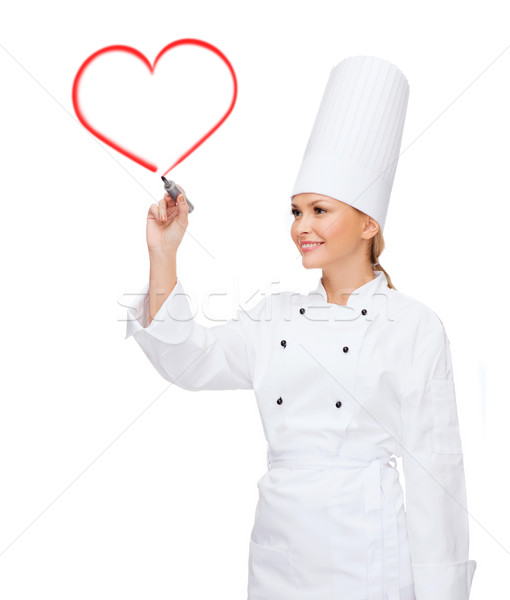smiling female chef writing something on air Stock photo © dolgachov