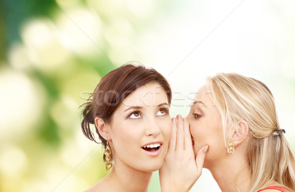 Stock photo: two smiling women whispering gossip