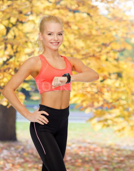 Donna sorridente frequenza cardiaca monitor mano fitness tecnologia Foto d'archivio © dolgachov