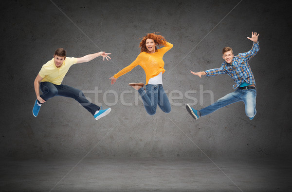 group of smiling teenagers jumping in air Stock photo © dolgachov