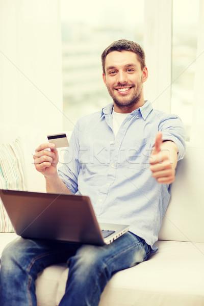 Sorridere uomo lavoro laptop carta di credito tecnologia Foto d'archivio © dolgachov