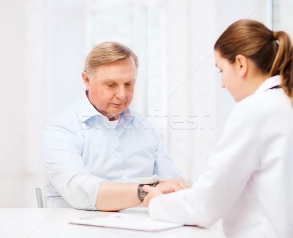 Női orvos nővér mér vérnyomás egészségügy Stock fotó © dolgachov