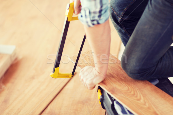 close up of male hands cutting parquet floor board Stock photo © dolgachov