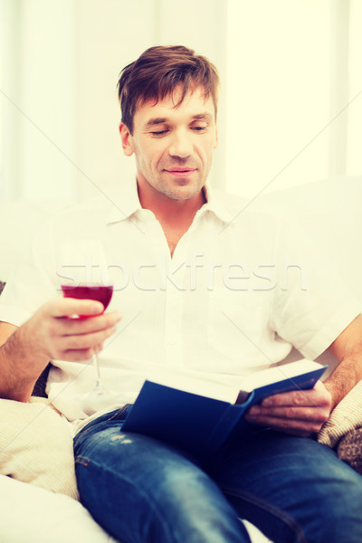 happy man with book and glass of rose wine at home Stock photo © dolgachov