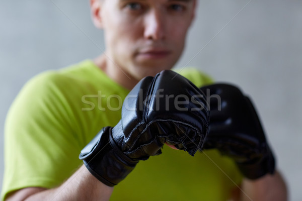 young man in boxing gloves indoors Stock photo © dolgachov