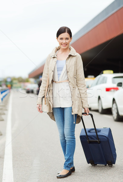 smiling young woman with travel bag over taxi Stock fotó © dolgachov
