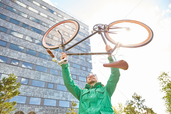 young hipster man rising fixed gear bike in city Stock photo © dolgachov