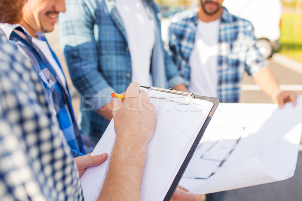 close up of builders with clipboard and blueprint Stock photo © dolgachov
