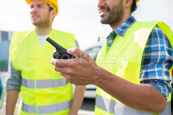 close up of builders in vests with walkie talkie Stock photo © dolgachov