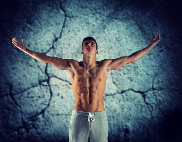 young male bodybuilder with raised hands Stock photo © dolgachov