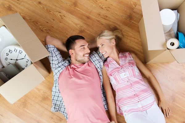 happy couple lying on floor among cardboard boxes Stock photo © dolgachov