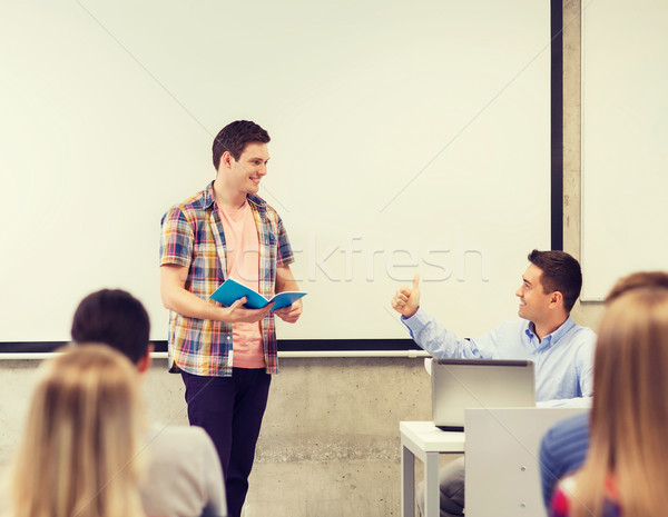 group of smiling students and teacher in classroom Stock photo © dolgachov