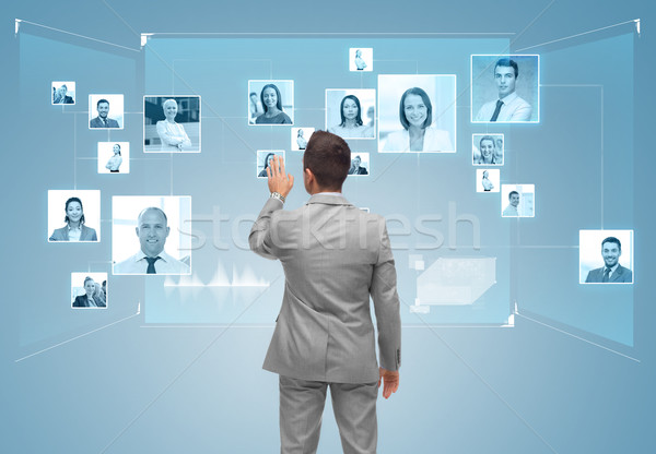 businessman with contacts icons on virtual screen Stock photo © dolgachov