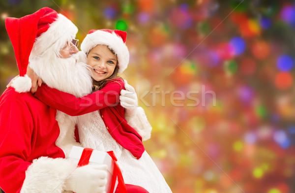 smiling girl cuddling with santa claus over lights Stock photo © dolgachov