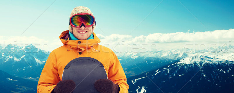happy young man in ski goggles over mountains Stock photo © dolgachov
