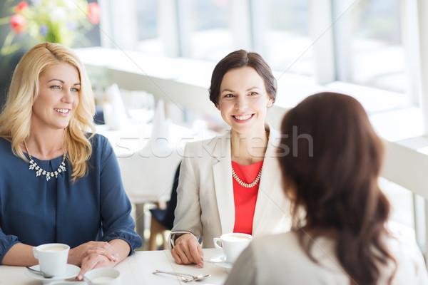 women drinking coffee and talking at restaurant Stock photo © dolgachov