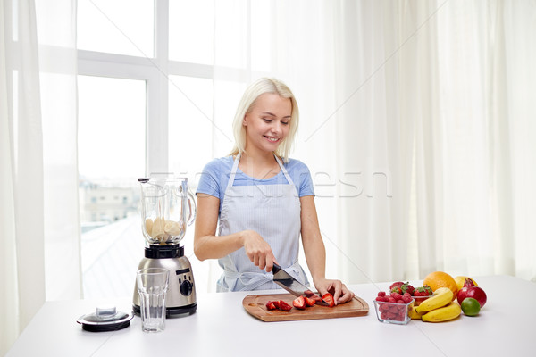 Stock photo: smiling woman with blender preparing shake at home