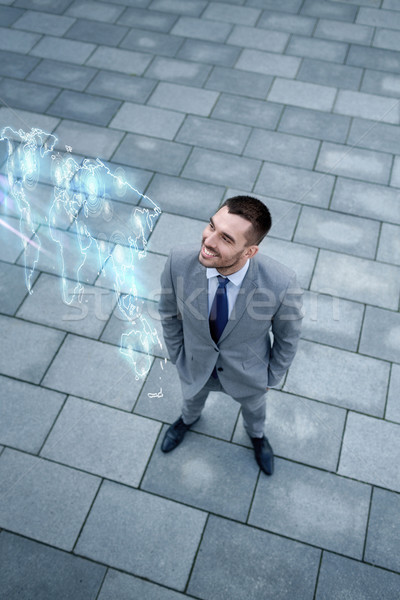 Zakenman wereldkaart hologram buitenshuis business ontwikkeling Stockfoto © dolgachov