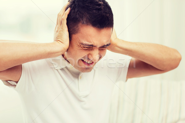unhappy man closing his ears by hands at home Stock photo © dolgachov