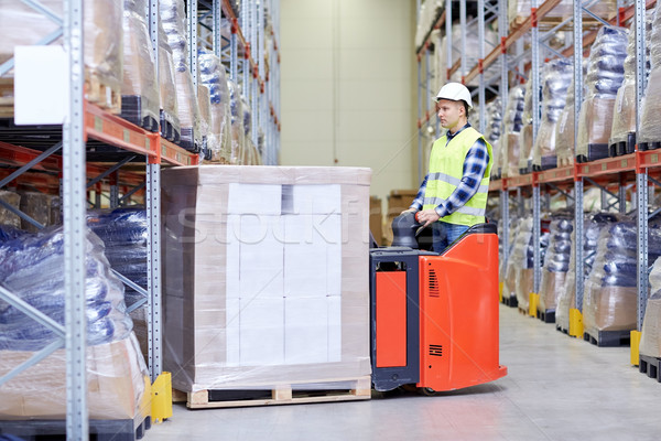 man on forklift loading boxes at warehouse Stock photo © dolgachov