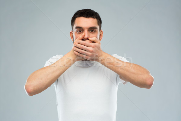man in white t-shirt covering his mouth with hands Stock photo © dolgachov