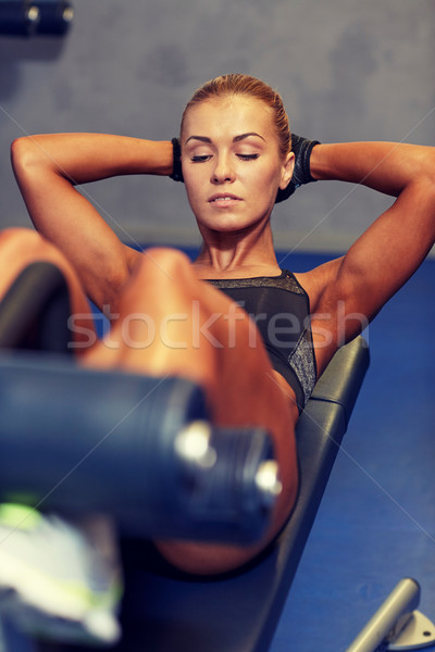 woman flexing abdominal muscles on bench in gym Stock photo © dolgachov