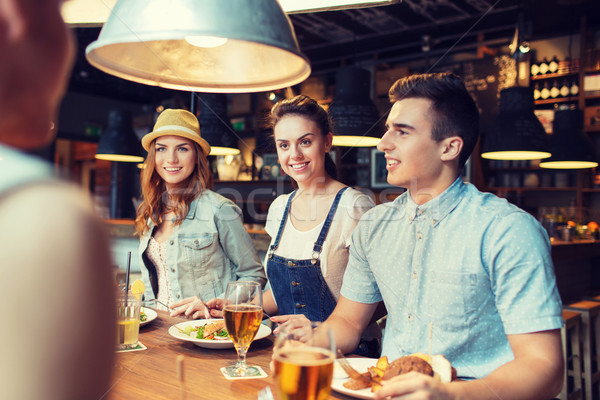 happy friends eating and drinking at bar or pub Stock photo © dolgachov
