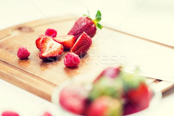 Közelkép érett piros eprek vágódeszka gyümölcsök Stock fotó © dolgachov