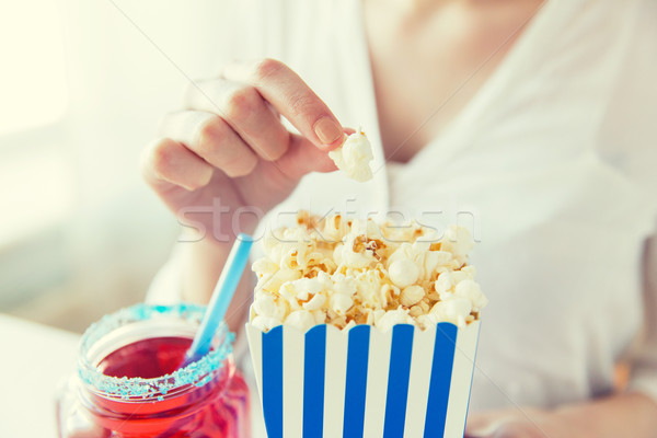 woman eating popcorn with drink in glass mason jar Stock photo © dolgachov