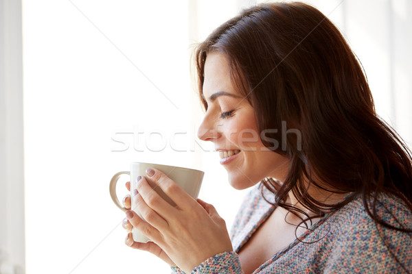happy woman with cup of tea or coffee at home Stock photo © dolgachov