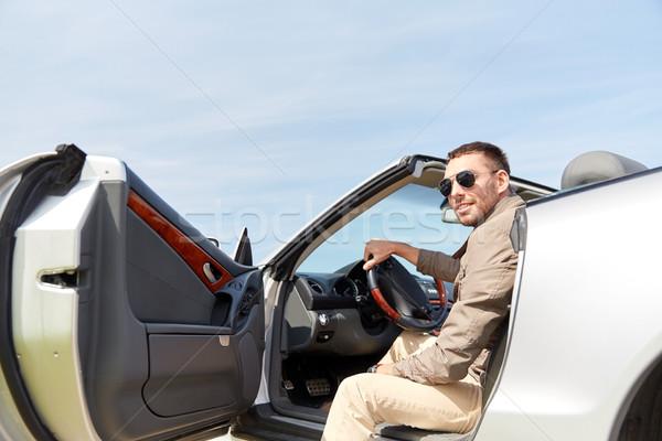happy man opening door of cabriolet car outdoors Stock photo © dolgachov