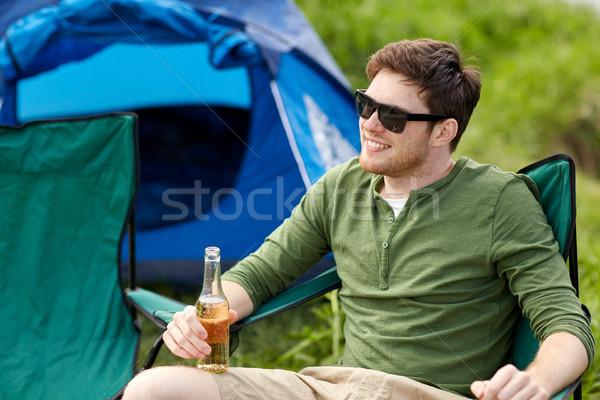 Boldog fiatalember iszik sör táborhely sátor Stock fotó © dolgachov