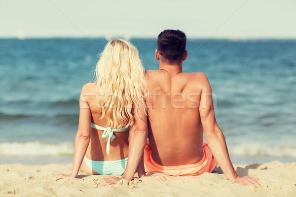 happy couple in swimwear sitting on summer beach Stock photo © dolgachov